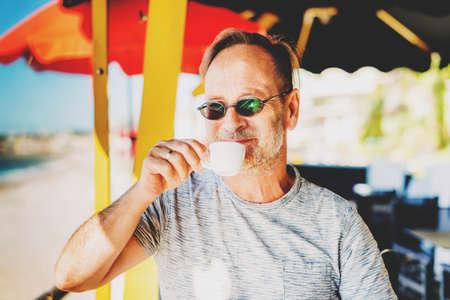 Knappe man drinken ochtend koffie bij een strand aan het strand restaurant