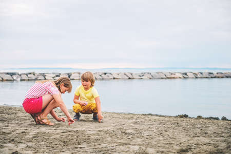 camargue: Cute little kids enjoying summer vacation by the sea. Image taken in Le Grau-du-Roi, Gard department, Camargue in Languedoc-Roussillon, France