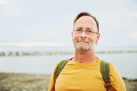 Hombre guapo en vacaciones de verano junto al mar, vistiendo camiseta amarilla safran y mochila