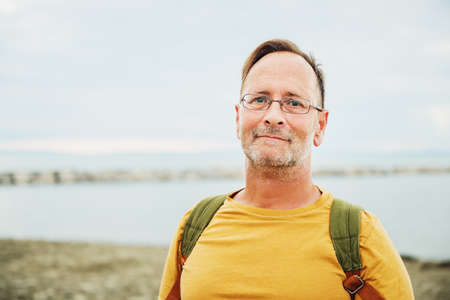 Handsome man on summer vacation by the sea, wearing yellow safran t-shirt and backpack