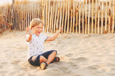 Funny kid boy resting on sand beach by the sea at sunset. Young child enjoying summer vacation on south of France, wearing polo, denim shorts and sandals shoes Stock Photo - 85485863