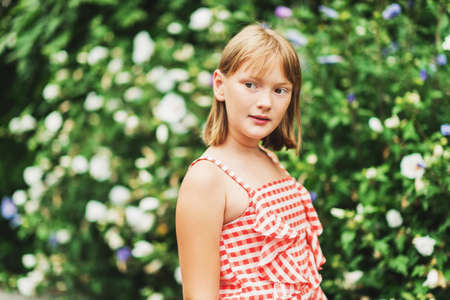Outdoor portrait of pretty little 9-10 year old girl wearing red gingham dress