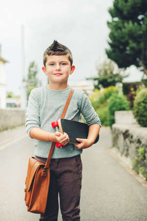 Outdoor portrait of funny little schoolboy wearing brown leather bag over shoulder, holding skateboard. Back to school concept. Film look toned image