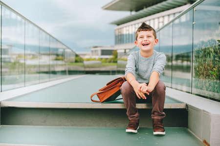zapatos escolares: Outdoor portrait of happy young kid boy. Fashion schoolboy resting outside. Back to school concept