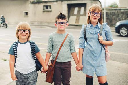 Groep van drie grappige kinderen dragen rugzakken lopen terug naar school. Meisje en jongens dragen bril in openlucht naast de weg Stockfoto