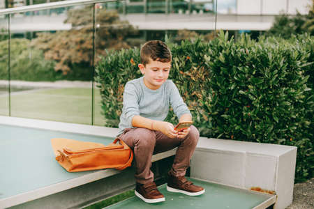 Outdoor portrait of cute little schoolboy playing with smartphone Stock Photo