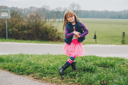 Outdoor portrait of little 5 year old girl in autumn, wearing pink tutu skirt