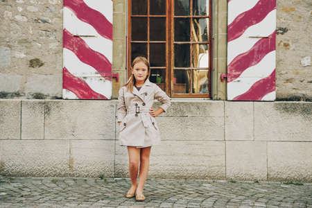 Outdoor fashion portrait of 8-9 year old hipster girl wearing stylish trench coat, posing against old window with vintage shutters Stock Photo
