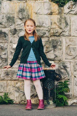 Outdoor portrait of a cute little girl wearing schoolwear