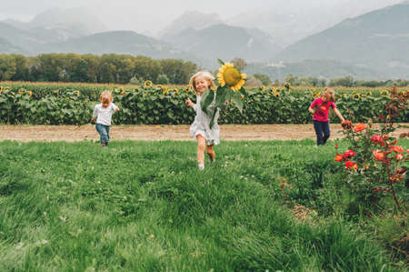 Group of 3 funny kids playing together in flower fields, vacation in countryside with children. Happy active childhood. Family enjoying nature in summer Archivio Fotografico