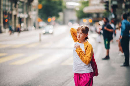 Outdoor portrait of pretty little teenage girl in a city, wearing yellow and white long sleeve baseball t-shirt and bright pink trousers