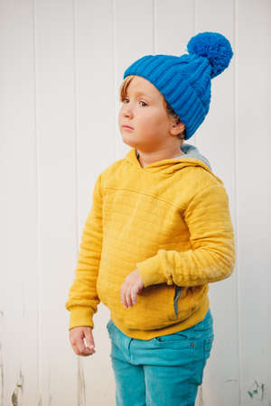 Stylish little 5 year old boy wearing blue hat, yellow (saffron or mustard color) hoody and cyan jeans