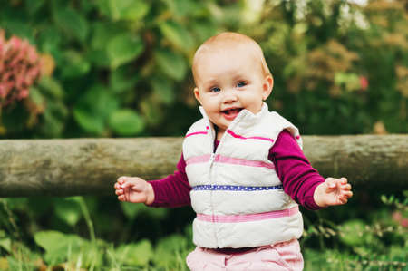 Outdoor portrait of adorable baby girl of 9-12 months old playing in the park, wearing white bodywarmer