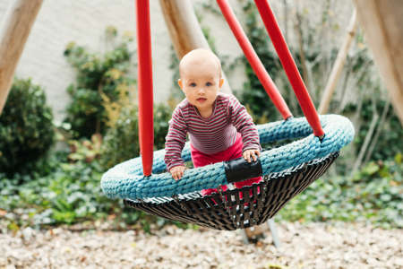 Baby girl having fun in the park, 9-12 months old kid playing in the big swing, summer playground, activities for children Stock Photo