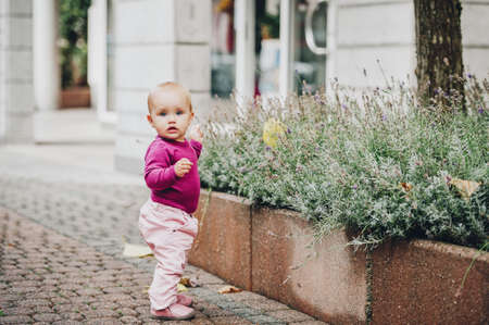 Adorable baby girl of 9-12 months old playing outside