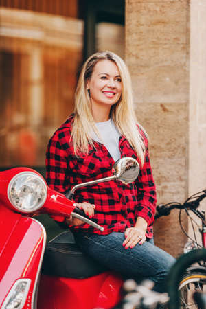 Outdoor portrait of beautiful blond woman wearing red plaid shirt