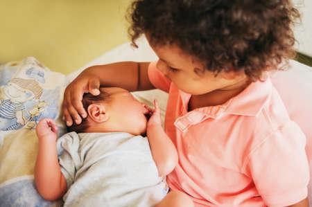 Eerste ontmoeting van schattige Afrikaanse peuterjongen en zijn pasgeboren broer in een prenataal ziekenhuis