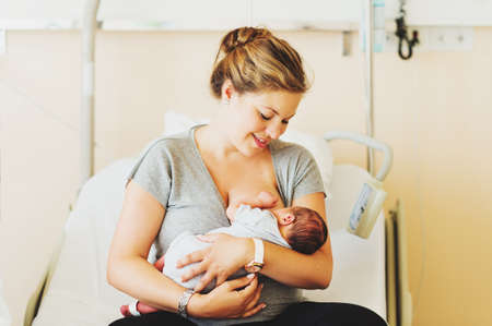 Happy young mother with newborn baby in hospital after giving birth Stockfoto
