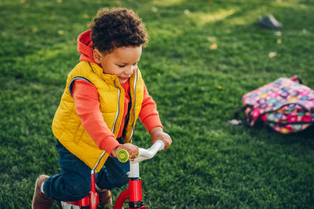 Outdoor portrait of cute little toddler boy playing in the park on a nice sunny day, wearing orange hoody jacket and yellow vest Stock Photo