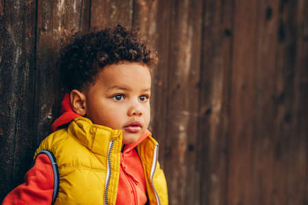 Outdoor portrait of adorable toddler boy posing outside against brown wooden background, wearing orange hoody jacket any bright yellow vest coat Stock Photo