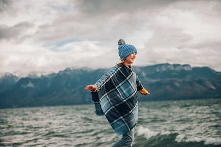 Sweet little girl playing by the lake on a very windy day, wearing blue hat and plaid poncho. Image taken on Lake Geneva, Lausanne, Switzerland