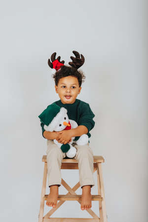 Christmas portrait of adorable toddler boy wearing green pullover, reindeer ears with Santa Claus hat, holding snowman toy, sitting on the high chair