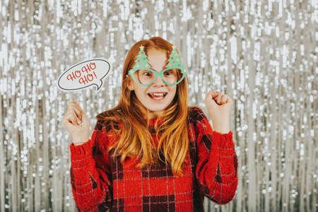 Kerstmisportret die van leuk meisje tegen zilveren achtergrond, rode trui dragen, feestelijke partijsteunen voor fotocabine houden Stockfoto