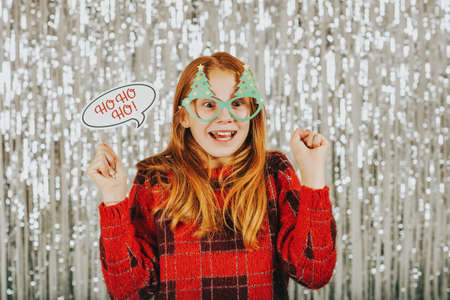Christmas portrait of cute little girl against silver background, wearing red pullover, holding festive party props for photo booth