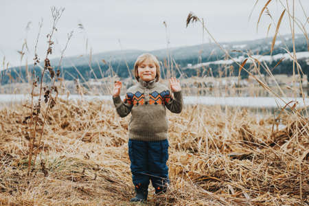 Outdoor portrait of a cute little boy of 4-5 years old, playing by the lake on a cold day Foto de archivo
