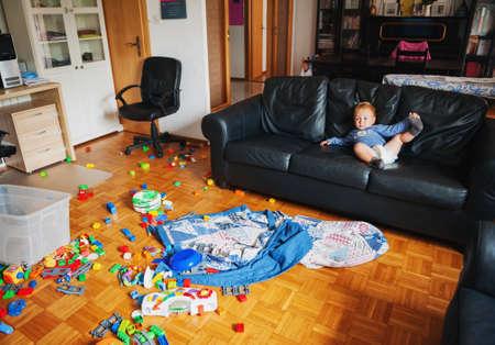 非常に厄介なリビングルームで遊んで面白い表情を持つ愛らしい1歳の男の子は、ソファに横たわって、テレビを見て