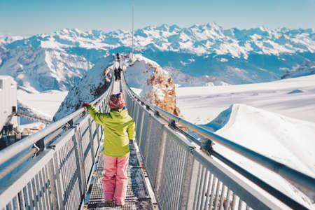 Jong geitjemeisje het spelen met sneeuw op de bovenkant van de berg, de wintervakantie met kinderen, familieactiviteiten in Alpen. Achteraanzicht. Afbeelding genomen in Glacier 3000, kanton Vaud, Zwitserland