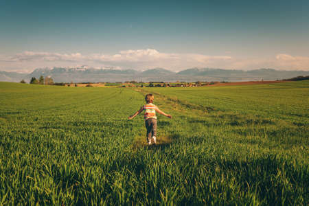 Adorable kid boy running in spring wheat field, arms wide open. Image taken in Canton of Vaud, Switzerland