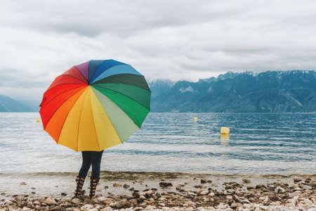 Child enjoying amazing view on Lake Geneva, Switzerland. Kid with huge colorful umbrella admiring mountains Standard-Bild