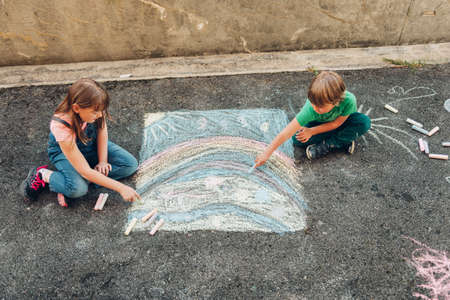 Two funny kids drawing with chalk, children playing together, top view Stok Fotoğraf