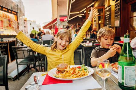 Feliz, crianças, comer, hamburger, com, batatas fritas, e, pizza, em, restaurante ao ar livre