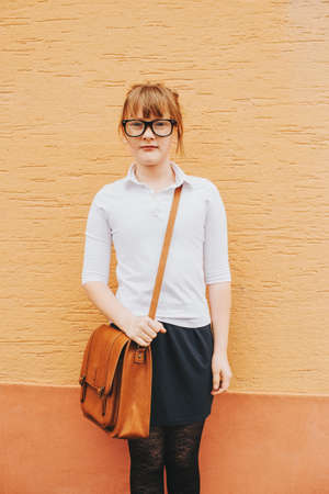 Pretty little 9 year old girl walking back to school, wearing white shirt, black skirt, eyeglasses and brown leather bag