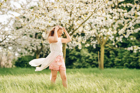 Pretty little kid girl playing in spring blooming garden Stock Photo