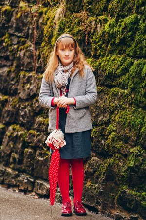Outdoor portrait of pretty 9-10 year old little girl, wearing grey coat and scarf, holding red polka dot umbrella
