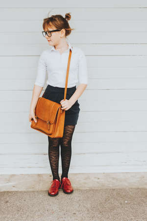 Pretty little 9 year old girl walking back to school, wearing white shirt, black skirt, red shoes, eyeglasses and brown leather bag