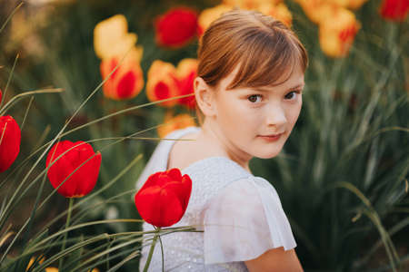 Spring portrait of sweet little girl wearing party dress, sitting outdoors with yellow and red tulips on background.