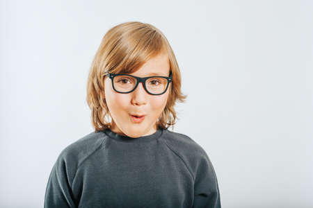 Studio shot of cute little boy wearing eyeglasses