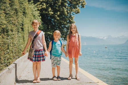 Group of 3 cute kids playing by the lake on a nice sunny day. Image taken on Lake Geneva, Lausanne, Switzerland