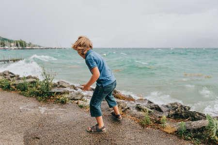 Sweet little boy playing by the lake on a very windy day wearing blue polo. Image taken on Lake Geneva, Lausanne, Switzerland Stock Photo