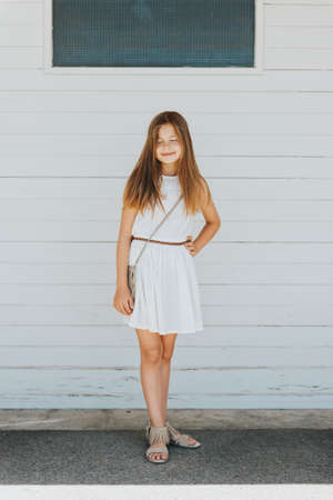 Outdoor portrait of adorable preteen girl wearing white summer dress