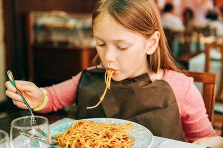 Adorable little girl eating spaghetti with bolognese sauce in the restaurant