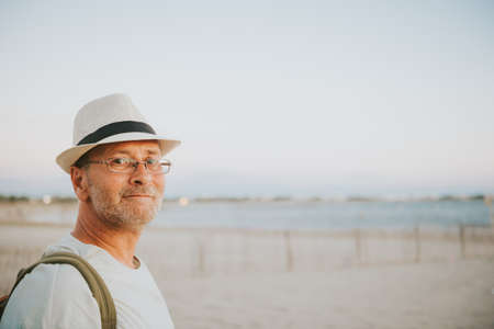 Handsome man on summer vacation by the sea, wearing hat, glasses and backpack