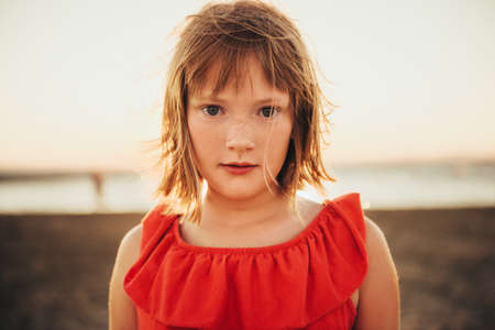 Close up portrait of sweet little girl with short bob haircut resting by the sea at sunset