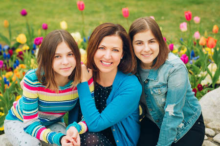 Outdoor portrait of happy mother and two young teenage girls