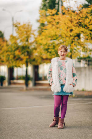 Outdoor fashion portrait of pretty kid girl wearing stylish pullover, white faux fur gilet and purple tights