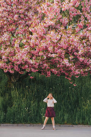 Spring image of blooming sakura. Kid girl playing with decorative cherry tree, happy childhood in countryside Foto de archivo - 100981497